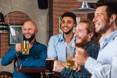 Man Group dans le football de sourire de barre et de observation heureux, tasses potables de prise de bière, amis gais de course  Photos stock