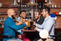 Man Group in de Glazen die van het Bargerinkel, het Drinken de Mokken van de Biergreep, Overhemden van de de Vriendenslijtage van Royalty-vrije Stock Foto
