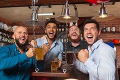 Man Group en el fútbol de griterío y de observación de la barra, tazas de consumición del control de la cerveza, amigos alegres d Imágenes de archivo libres de regalías