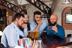 Man Group na cerveja bebendo da barra, Guy Hold Cell Smart Phone frustrante imagem de stock royalty free
