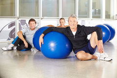 Man in group of senior people with gym ball. Man sitting in group of senior people with gym ball in a fitness center Stock Image