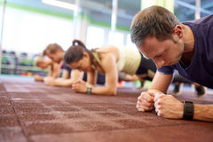 Man at group training doing plank exercise in gym. Fitness, sport, exercising and people concept - men with heart-rate tracker at group training doing plank Stock Image