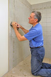 Man grouting ceramic tile in bathroom Royalty Free Stock Photography