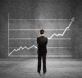 Man and growth chart. Businessman looks at growth chart Stock Images