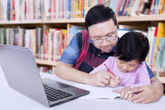 Man guide a girl to write on the book. Photo of young asian men guide a little girl to learn and write on the book, shot in the library Stock Photo