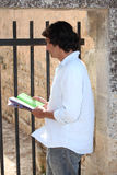 Man with a guidebook. Watching something stock image