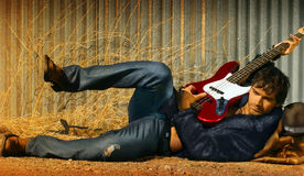 Man and Guitar. Horizontal full body portrait of hot young guy in fur playing electric guitar Royalty Free Stock Photos