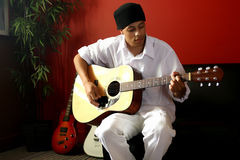 Man with Guitar. Attractive Male Musican Plays his Acoustic Guitar Stock Photo