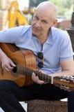 Man with guitar. Adult man playing guitar outdoors Stock Image