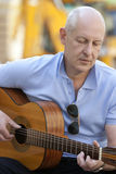 Man with guitar. Adult man playing guitar outdoors Royalty Free Stock Image