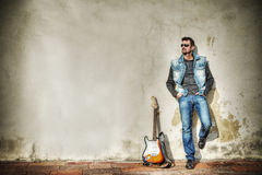 Man and guitar against a grungy wall in hdr Stock Photo