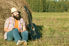 Man with guitar and beer on nature Royalty Free Stock Photos