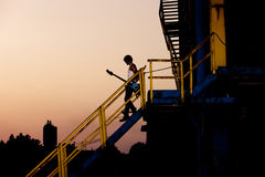 Man with guitar at dusk Stock Images