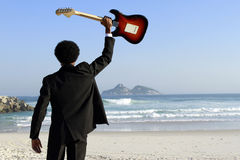 Man with guitar. Eletric on the beach Stock Photography