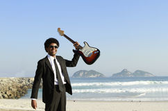 Man with guitar. Eletric on the beach Stock Images