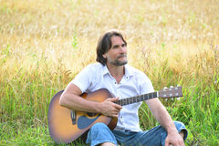 Man with a guitar in a field Stock Image