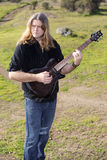 Man with guitar on a field Royalty Free Stock Photo
