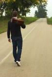 Man with guitar going forward. Royalty Free Stock Photos