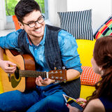 Man with guitar. Handsome smiling men playing acoustic guitar on the yellow couch at home Stock Images