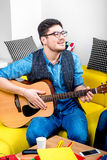 Man with guitar. Handsome smiling man playing acoustic guitar on the yellow couch at home Royalty Free Stock Photos