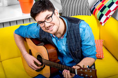 Man with guitar. Handsome smiling man playing acoustic guitar on the yellow couch at home Stock Photography