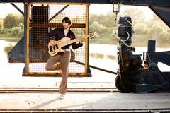 Man and guitar at industrial port Stock Photos