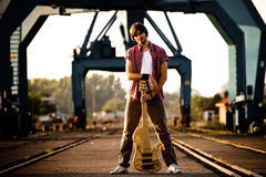 Man and guitar at industrial port Royalty Free Stock Photography