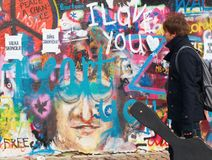 A man with a guitar is looking for new paintings on  Lennon Wall in Prague on Kampa Stock Image