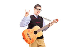 Man with a guitar making a rock and roll hand sign. Young man with an acoustic guitar making a rock and roll hand sign isolated on white background Royalty Free Stock Photography