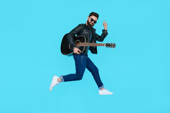 Man guitar player jumps while showing rock gesture Royalty Free Stock Photo