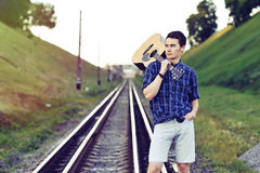 Man with guitar on railway road Stock Photos