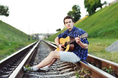 Man with guitar on railway road Royalty Free Stock Image