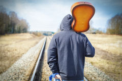 Man with guitar on the railway Stock Images
