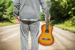 Man with guitar on rural road Royalty Free Stock Images