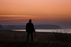 Man with guitar in sunset Royalty Free Stock Photography