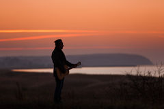Man with guitar in sunset Royalty Free Stock Images
