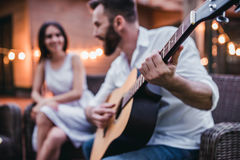 Man with guitar on terrace. Beautiful couple is sitting on house`s terrace and smiling. Man is playing guitar royalty free stock photo