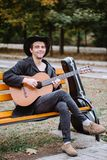 Man with guitar. Vertical portraig young man with acoustic guitar on bench in the park stock photography