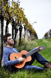 Man with guitar on vineyard Stock Photos