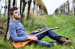 Man with guitar on vineyard Stock Images
