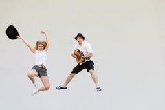 Man with guitar and woman jumping Stock Photos