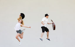 Man with guitar and woman jumping Stock Photo