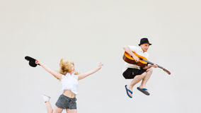 Man with guitar and woman jumping Royalty Free Stock Image