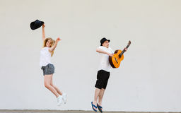 Man with guitar and woman jumping Royalty Free Stock Images