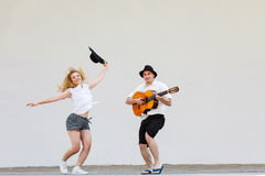Man with guitar and woman jumping Stock Images