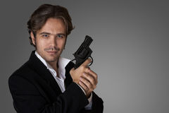A man with a gun. In the hands of the studio on a gray background Royalty Free Stock Photos