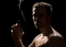 Man with a gun. A man with a gun and smoke over the gun on black background Stock Photography