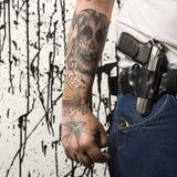 Man with gun. Caucasian tattooed man wearing holster with gun stock photos