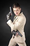 Man with a gun. Handsome man with a gun wearing a white suit Stock Photos