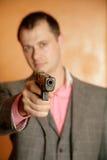 Man with gun. Man in grey suit on orange background holding gun - selective focus on gun Royalty Free Stock Photos